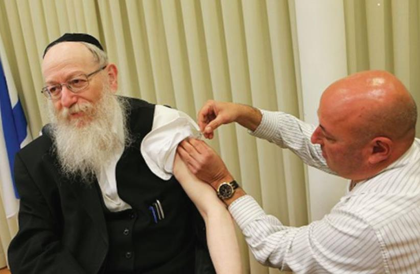 HEALTH MINISTER Yaacov Litzman receives his flu shot from Prof. Itamar Grotto (photo credit: HEALTH MINISTRY)