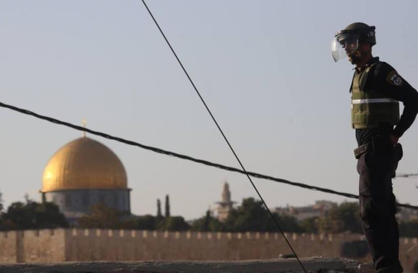 A Border Police officer overlooks Temple Mount and the Western Wall (photo credit: MARC ISRAEL SELLEM)