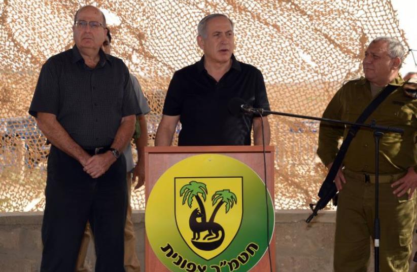 Prime Minister Benjamin Netanyahu (C) visits troops near Gaza border with Defense Minister Moshe Ya'alon (L) and IDF Chief of Staff Lt.-Gen. Gadi Eisenkot (R) (file photo) (photo credit: CHAIM TZACH/GPO)