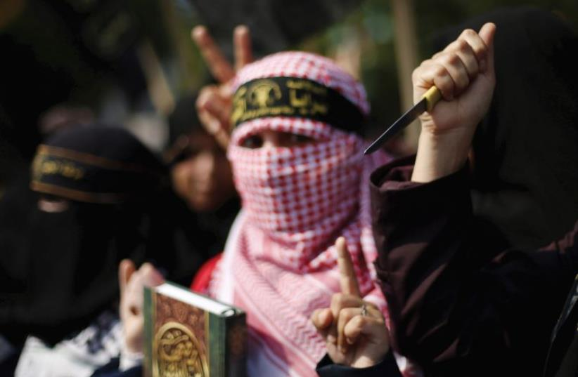 A PALESTINIAN woman holds up a knife in the Gaza Strip. (photo credit: REUTERS)