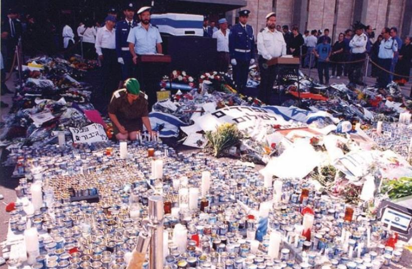 A soldier organizes memorial candles in front of Yitzhak Rabin's casket, at the Knesset in November 1995 (photo credit: ISAAC HARARI)
