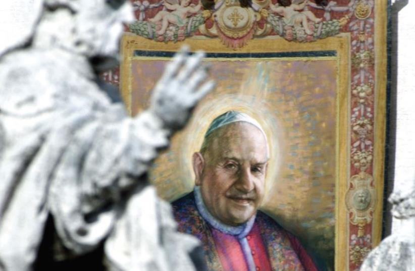 A TAPESTRY with the image of Pope John XXIII hangs on the facade of St. Peter's facade during a beatification ceremony in 2000. (photo credit: REUTERS)