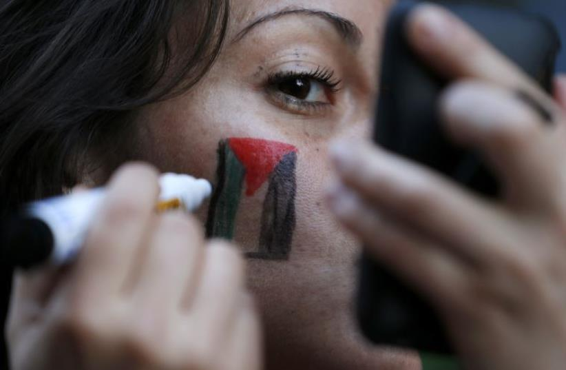A member of the Palestinian community in Chile paints a Palestinian flag on her face during a protest against Israel's military operations in Gaza (photo credit: REUTERS)