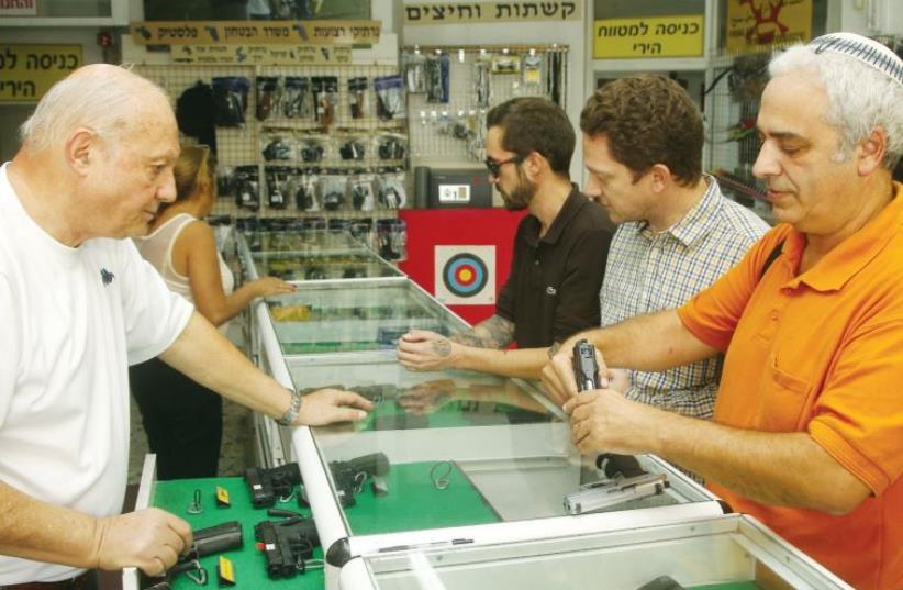 Magnum 2525 owner Itzik Mizrahi shows a Beretta handgun to customers in Jerusalem (photo credit: MARC ISRAEL SELLEM/THE JERUSALEM POST)