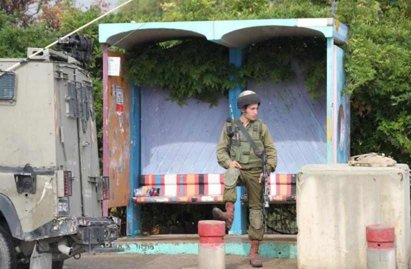 A soldier by a bus stop at the Gush Etzion junction (photo credit: TOVAH LAZAROFF)