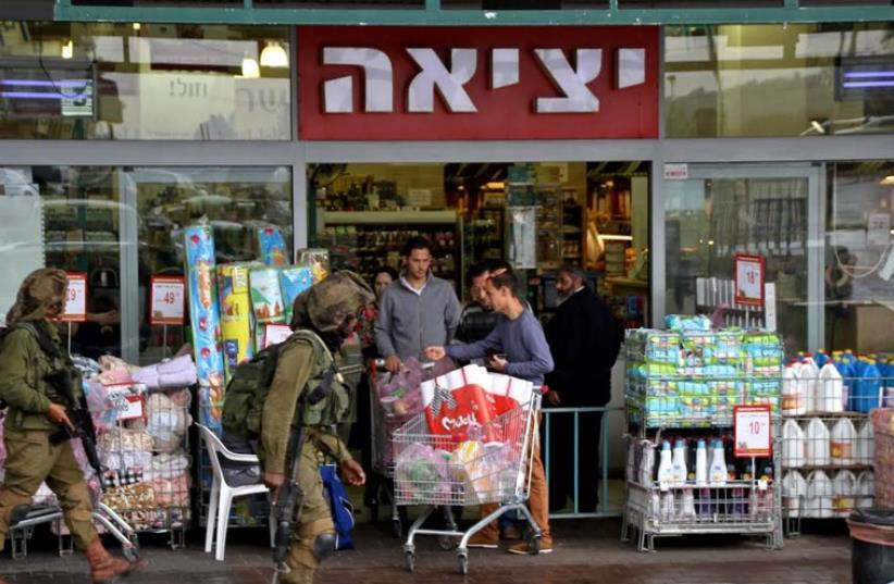 Soldiers patrolling the parking lot by the Rami Levi supermarket in the Gush Etzion commercial center (photo credit: TOVAH LAZAROFF)