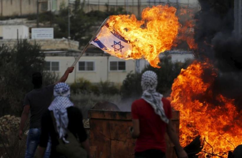 A Palestinian demonstrator sets fire to an Israeli flag near the West Bank settlement of Beit El (photo credit: REUTERS)