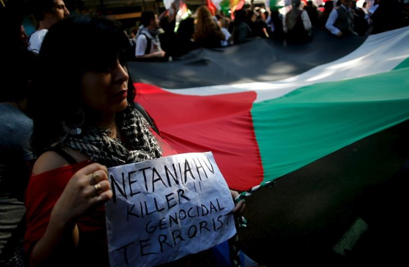 A protester holds a sign against Prime Minister Benjamin Netanyahu during a pro-Palestinian demonstration outside the Israeli Embassy in Buenos Aires, October 30, 2015 (photo credit: REUTERS)
