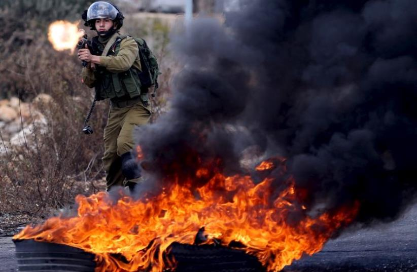 An Israeli soldier fires a weapon towards Palestinian protesters during clashes near the Jewish settlement of Beit El (photo credit: REUTERS)
