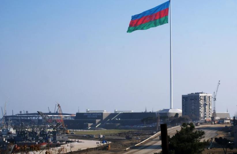 An enormous Azerbaijani flag flies above the construction site of a landmark concert hall on the Caspian Sea shoreline in Baku (photo credit: SAMIR ALIYEV/AFP)