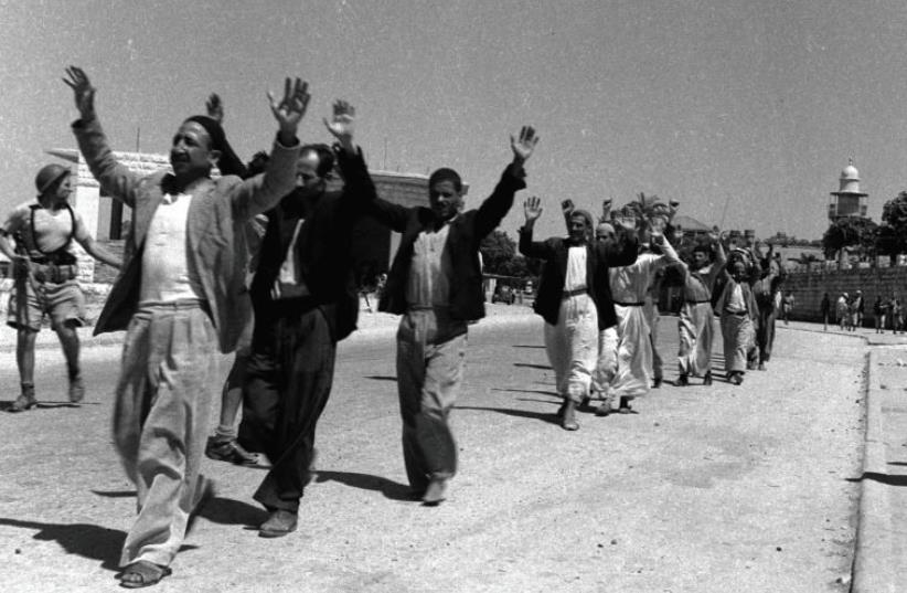 ARAB RESIDENTS of the town of Ramle, southeast of Tel Aviv, raise their hands in surrender to Israeli soldiers in July of 1948. Did the Mufti represent them? (photo credit: REUTERS)