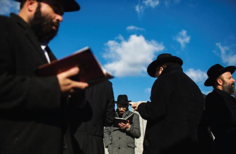 MEN PRAY at the gravesite of the Lubavitcher Rebbe, Rabbi Menachem M. Schneerson, in the Queens borough of New York Last November. (photo credit: REUTERS)