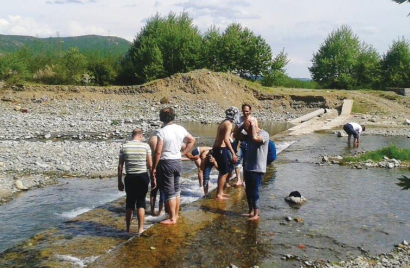 Samir and his companions bathe in a stream in Macedonia (photo credit: Courtesy)