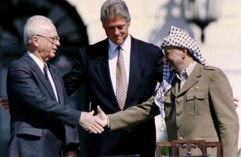 Then-PLO Chairman Yasser Arafat (R) shakes hands with then-prime minister Yitzhak Rabin (L), as U.S. President Bill Clinton stands between them (photo credit: REUTERS)