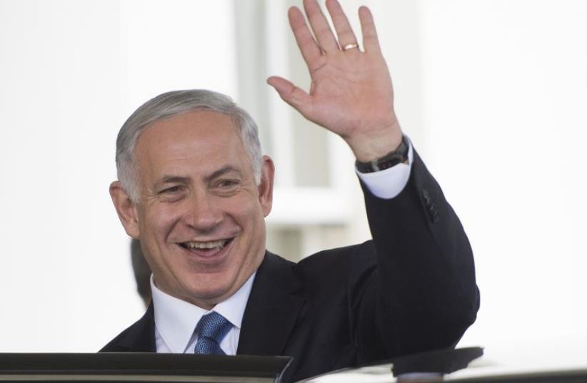 Prime Minister Benjamin Netanyahu waves after meeting President Barack Obama at the White House in Washington, October 1, 2014 (photo credit: AFP PHOTO)