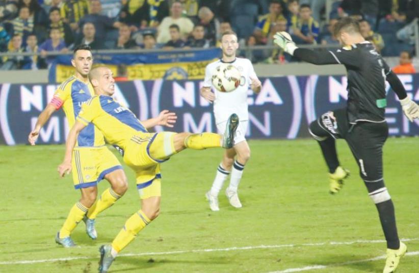 Maccabi Tel Aviv forward Tal Ben-Haim (left) chips Maccabi Netanya goalkeeper Barak Levy to score his team's second goal in last night's 2-1 win at Bloomfield Stadium.  (photo credit: ADI AVISHAI)