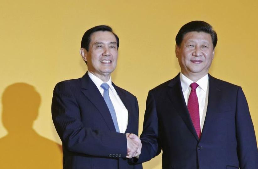 CHINESE PRESIDENT Xi Jinping shakes hands with Taiwan's President Ma Yingjeou during a summit in Singapore on November 7. (photo credit: REUTERS)