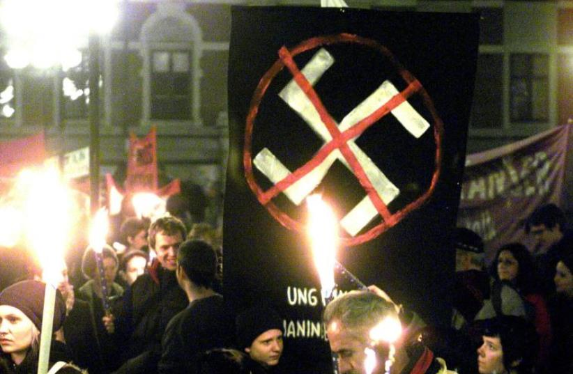 Some thousand people hold banners and torches as they gather in the Maria Square in Stockholm on November 9, 2000, to protest against racism on the anniversary of the Kristallnacht (photo credit: BERTIL ERICSON / SCANPIX SWEDEN / AFP)