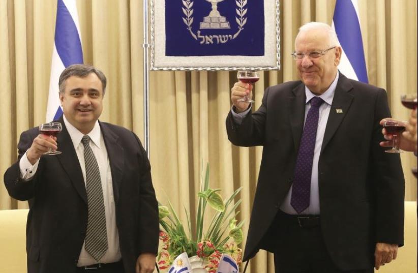 PRESIDENT REUVEN RIVLIN toasts Uruguay's ambassador, Nestor Alejandro Rosa Navarro, who presented his credentials for a second stint yesterday in Jerusalem. (photo credit: MARC ISRAEL SELLEM)