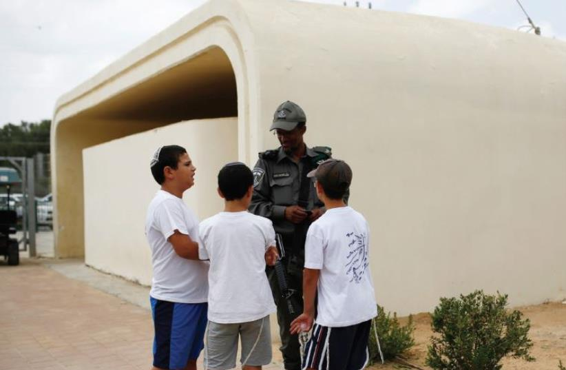 SCHOOLCHILDREN CHAT with a member of the Border Police near a bomb shelter at Kibbutz Sa'ad (photo credit: REUTERS)