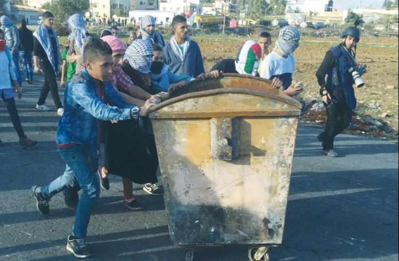 PALESTINIAN PROTESTERS push a dumpster toward the DCO checkpoint near Ramallah (photo credit: SETH J. FRANTZMAN)