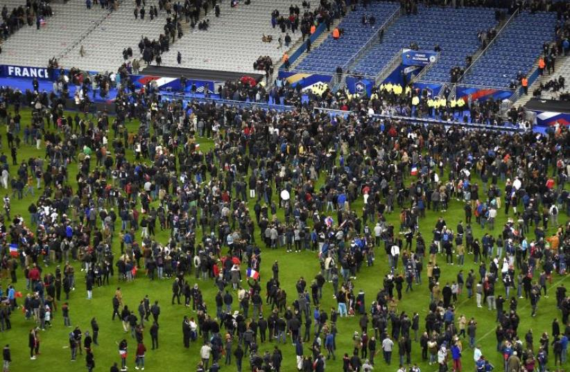 Soccer fans wait for security clearance to leave the Stade de France in Saint-Denis, north of Paris, after the friendly football match France vs Germany on November 13, 2015 (photo credit: PHOTO/FRANCK FIFE)