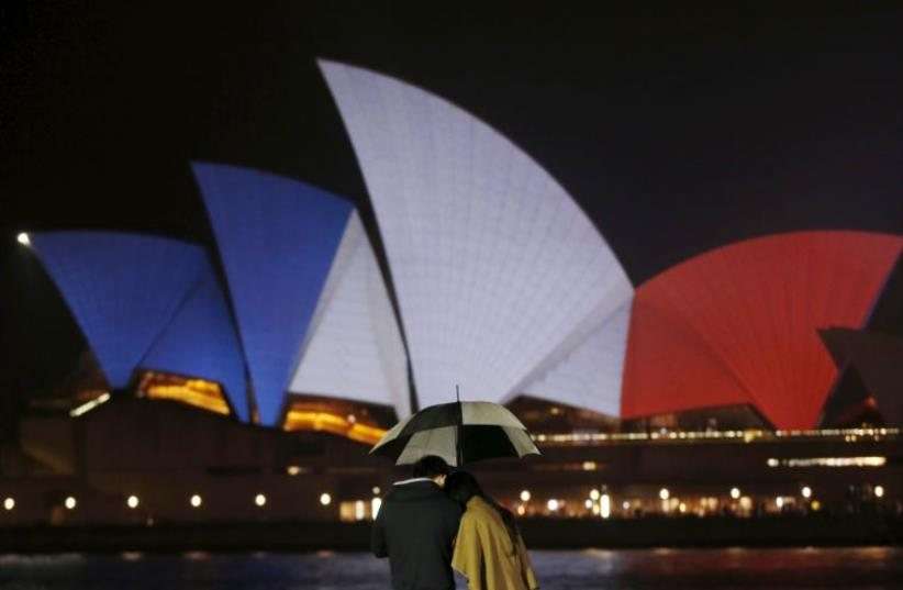 Colors of France's national flag are projected onto the sails of Sydney's Opera House in Australia November 14, 2015, following the attacks in Paris.  (photo credit: REUTERS)