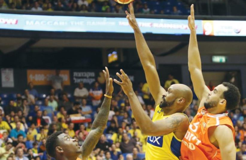Maccabi Tel Aviv forward Devin Smith (center) attempts a shot during his team's win over Ironi Ness Ziona at Yad Eliyahu Arena (photo credit: ADI AVISHAI)