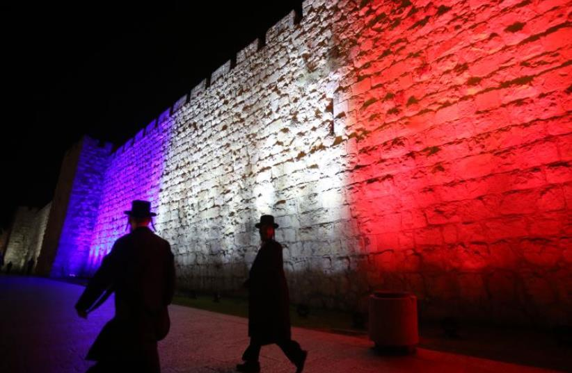 Wall of Jerusalem's old city lit up in colors of French flag (photo credit: MARC ISRAEL SELLEM/THE JERUSALEM POST)
