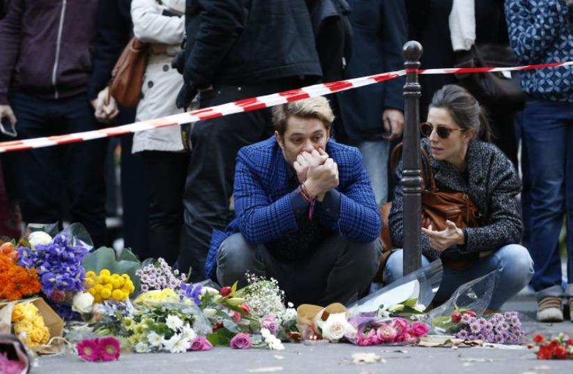 """Mourners gather at memorial sites outside of the Casa Nostra restaurant and the cafe """"Bonne biere"""" in Paris, on November 15, 2015, following a series of coordinated attacks in and around Paris on November 13 (photo credit: PATRICK KOVARIK / AFP)"""