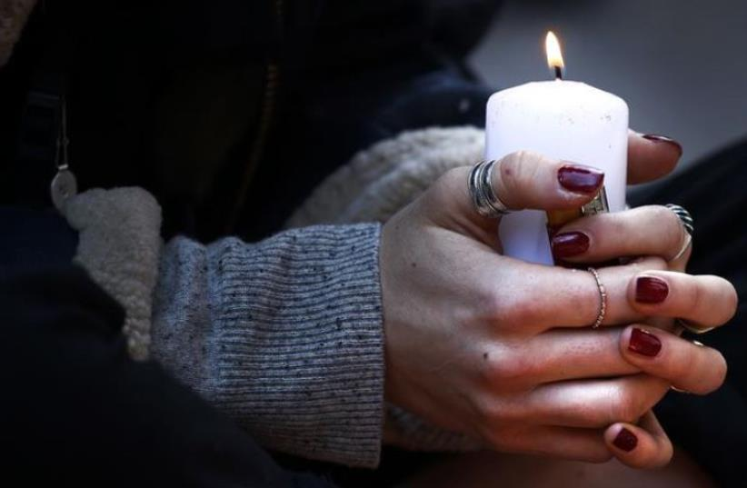 A woman holds a candle as she pays her respect at one of the attack sites in Paris, November 15, 2015.  (photo credit: REUTERS)