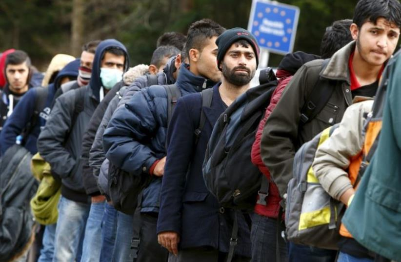 Migrants stay in a queue before passing the Austrian-German border (photo credit: REUTERS)