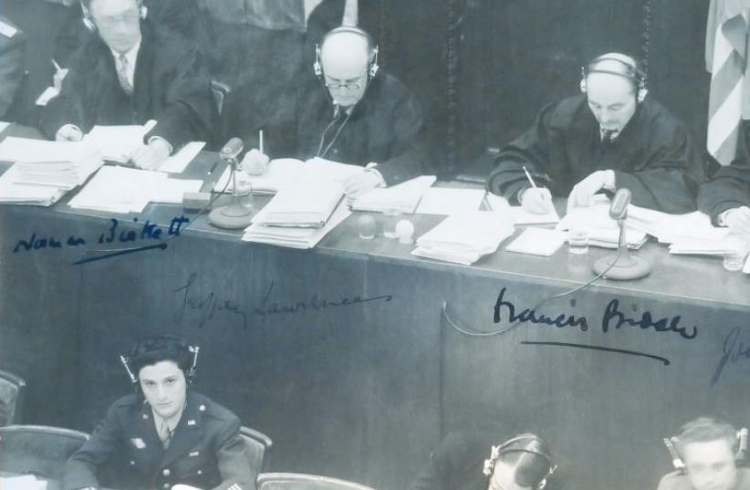 George Sakheim at left, in front of judges at Nuremberg Trial, 1946. The photo was signed by British and American judges (photo credit: COURTESY GEORGE SAKHEIM)