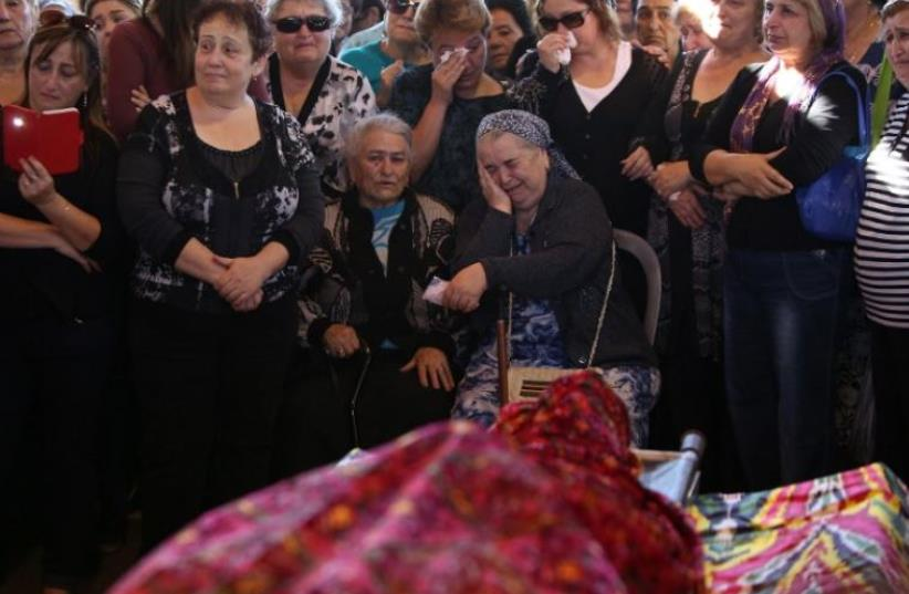 Relatives and friends mourn during the funeral of Reuven Aviram, 51, who died during an stabbing attack in Tel Aviv, November 19, 2015 (photo credit: AFP PHOTO)