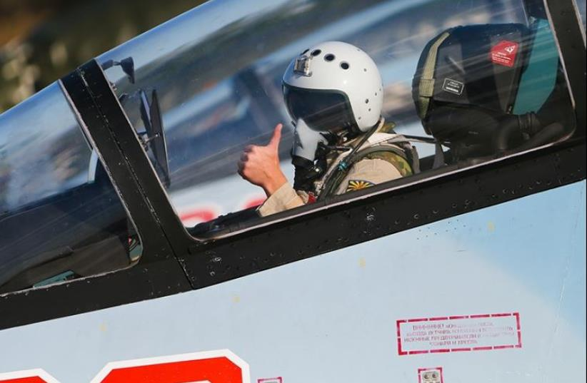 A Russian pilot gives the thumbs-up sign on an airbase in Syria (photo credit: RUSSIAN ARMED FORCES)