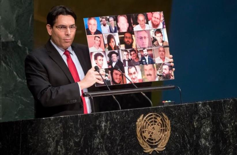 Israel's ambassador to the UN, Danny Danon, holds up a collage of Israeli victims of Palestinian terrorism (photo credit: UN)