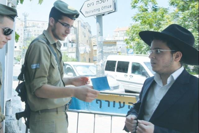 A HAREDI MAN shows his call-up notice to soldiers to allow him entry to the Jerusalem recruitment office (photo credit: MARC ISRAEL SELLEM)