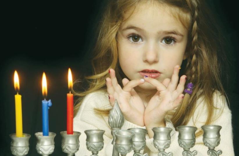 A young girl lights a hanukkia (photo credit: ILLUSTRATIVE: MARC ISRAEL SELLEM)