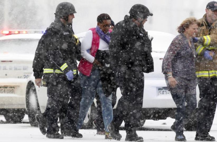Two women are evacuated from a building where a shooter was suspected to be still holed up in Colorado Springs, Colorado November 27, 2015 in a driving snow storm.  (photo credit: REUTERS)