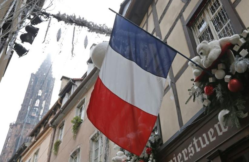 A French flag hangs from a window of a restaurant decorated for Christmas holiday season in Strasbourg, France (photo credit: REUTERS)
