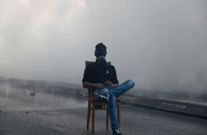 A Palestinian protester sits in middle of a road as Israeli troops fire tear gas during clashes in the West Bank city of Bethlehem (photo credit: REUTERS)