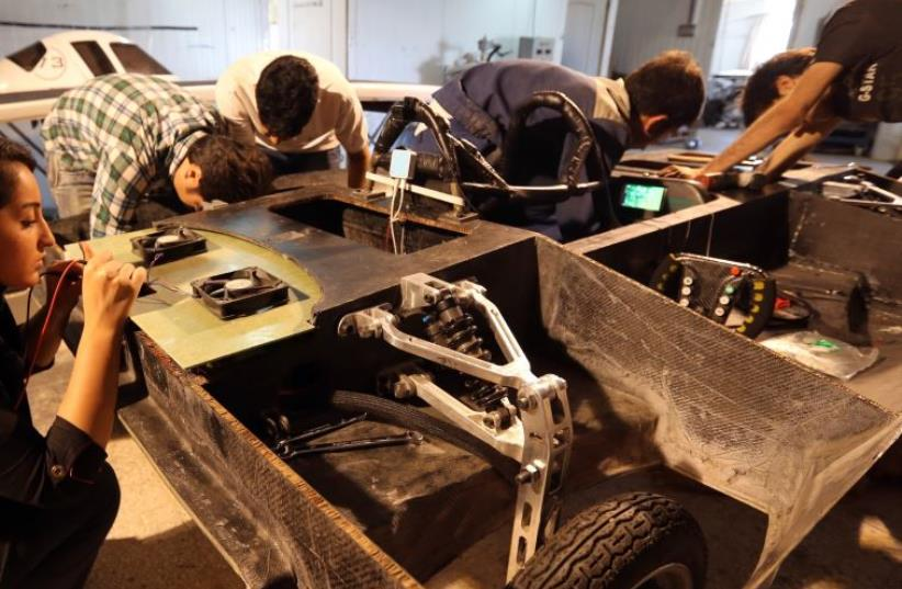 Students at Qazvin Azad Islamic University, west of Tehran, assemble a solar-powered Havin-2 vehicle for a test drive (photo credit: ATTA KENARE / AFP)
