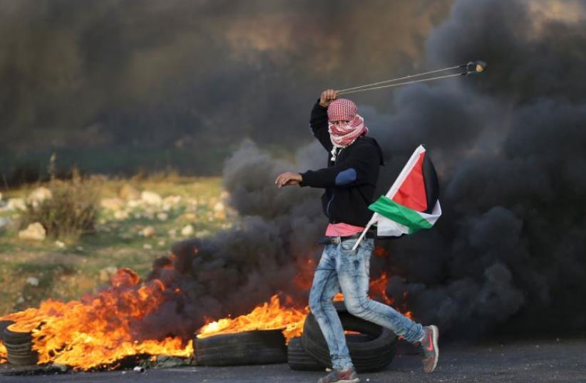 A Palestinian protester uses a sling to throw stones towards Israeli troops during clashes, near the Jewish settlement of Bet El, near the West Bank city of Ramallah November 29, 2015 (photo credit: REUTERS)