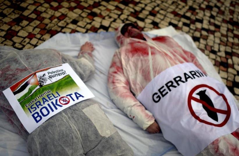 """Demonstrators lie with posters in Basque which read, """"Up With Palestinians. Boycott Israel"""" (L) and """"No To War"""" as they wear suits covered in fake blood during a pro-Palestinian protest at the Plaza Moyua in Bilbao (photo credit: REUTERS)"""