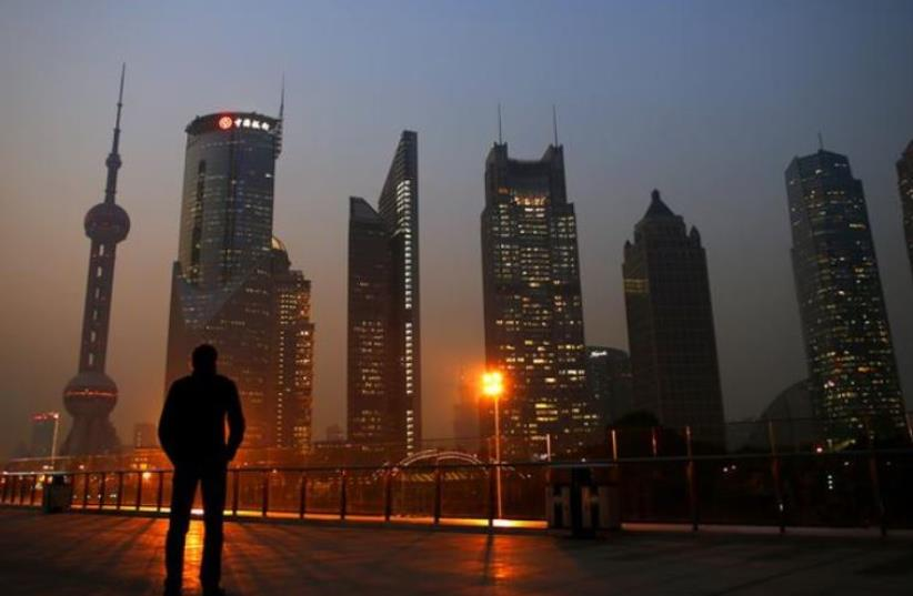A man looks at the Pudong financial district of Shanghai November 20, 2013. (photo credit: REUTERS)