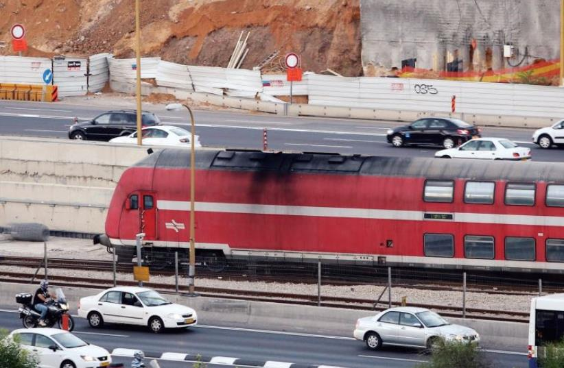 A train runs parallel to the Ayalon Highway in Tel Aviv (photo credit: MARC ISRAEL SELLEM/THE JERUSALEM POST)