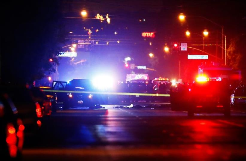 Police vehicles line the street around a vehicle in which two suspects were shot following a mass shooting in San Bernardino, California (photo credit: REUTERS)