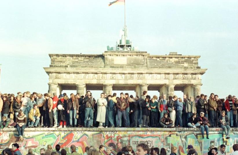 West Berlin citizens continue their vigil atop the Berlin Wall in front of the Brandeburg Gate in this November 10, 1989 file photo (photo credit: REUTERS)