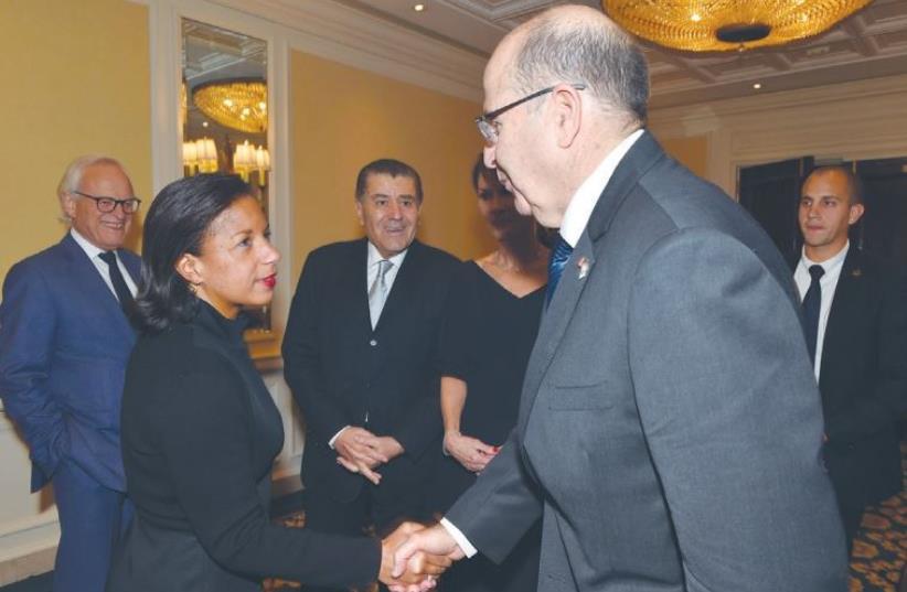 DEFENSE MINISTER Moshe Ya'alon shakes hands with US National Security Adviser Susan Rice at the Saban Forum in Washington as Haim Saban (center) looks on (photo credit: ARIEL HERMONI / DEFENSE MINISTRY)