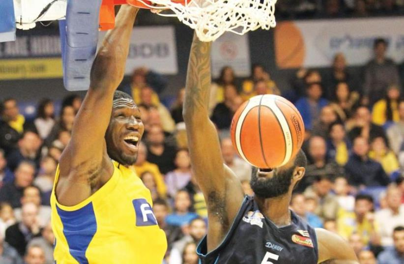 Maccabi Tel Aviv forward Trevor Mbakwe (left) dunks over Hapoel Eilat's C.J. Leslie during last night's 96-69 yellow-and-blue blowout in BSL action at Yad Eliyahu Arena (photo credit: DANNY MARON)